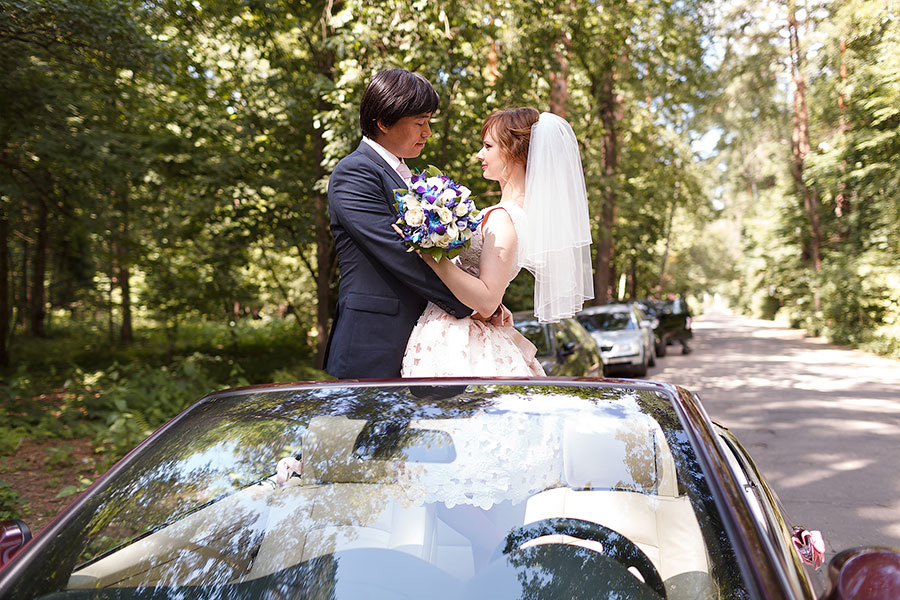 Жених и невеста в красном кабриолете
